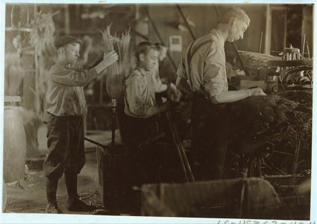 Boys assisting at the Broom Machines. S. W. Brown Mfg. Co.,.  Location: Evansville, Indiana.