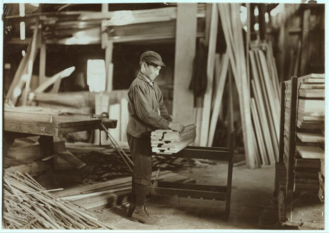 Boy probably about 13 years old, tying strips which he has taken away from the planer. Schultze Waltum Co., Planing Mill.  Location: Evansville, Indiana.