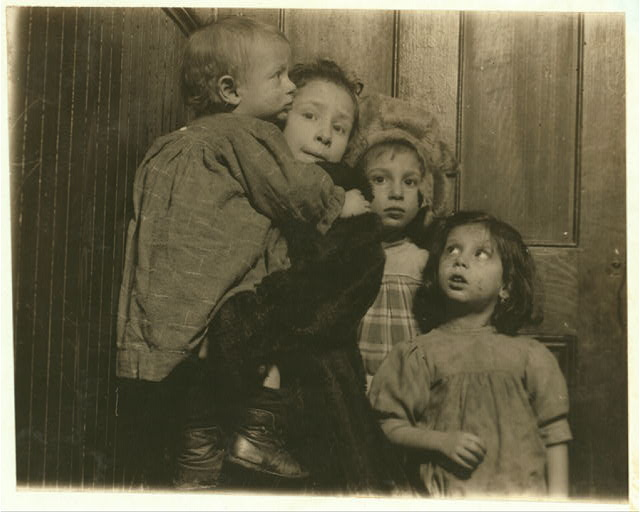 3:30 P.M. Group in tenement hallway. Ages, 14 months, 2, 5, and 7 years. Mother in shop sewing. Father out of work, bartender. Family, Novi, 189 Chrystie Street.  Location: New York, New York (State)