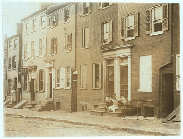 Group of children playing on the stoop of a house next to 229 Tatnall St., a reputed house of prostitution. Investigator, Edward F. Brown.  Location: Wilmington, Delaware