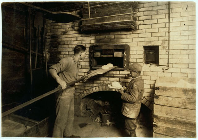 [Vincenzo Messina, 15 years old and brother Angelo, 11 years old, baking bread for father, 174 Salem Street. Vincenzo is working nights now, from 5 P.M. to 5 P.M. Usually works on day shift. Angelo helps a great deal, tends store and helps bake too.]  Location: [Cambridge, Massachusetts]