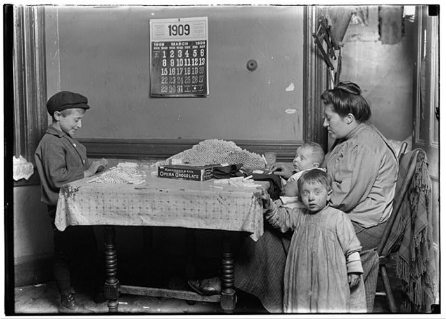 Widow & boy rolling papers for cigarettes in a dirty N.Y. tenement. Location: New York, New York (State)