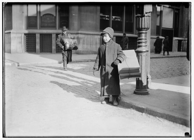 Ten-year-old child carrying a box of artificial leaves from Leroy St. across B'[road]way, New York.  Location: New York, New York (State)