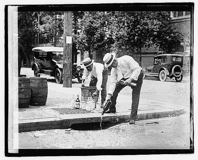 [Two men pouring liquor into storm drain], 7/8/21