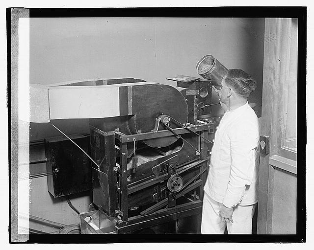 [Man with unidentified machine, possibly a blower or enlargement print dryer]
