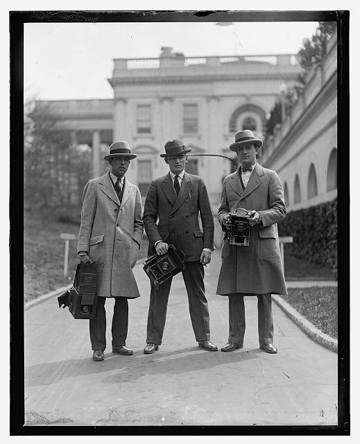 [Three men with cameras outside White House]