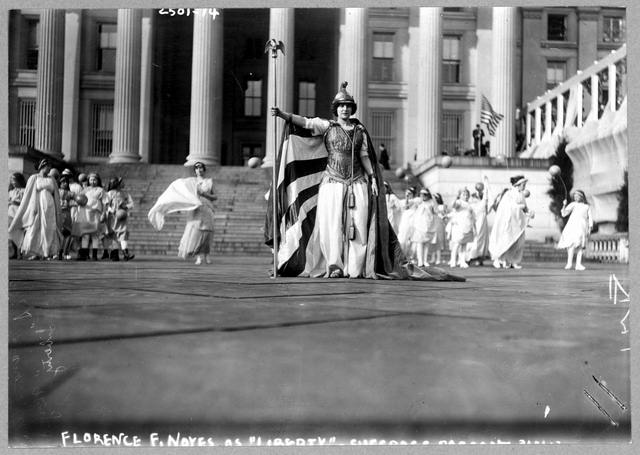 "[German actress Hedwig Reicher wearing costume of ""Columbia"" with other suffrage pageant participants standing in background in front of the Treasury Building, March 3, 1913, Washington, D.C.]"