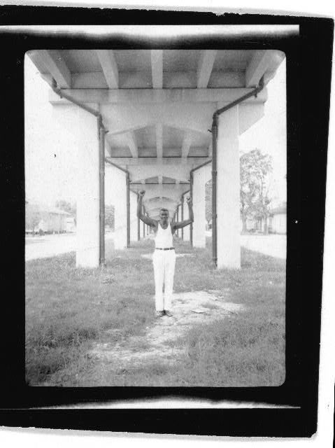 [John Bray, standing with hands raised underneath a bridge, Amelia, Louisiana]