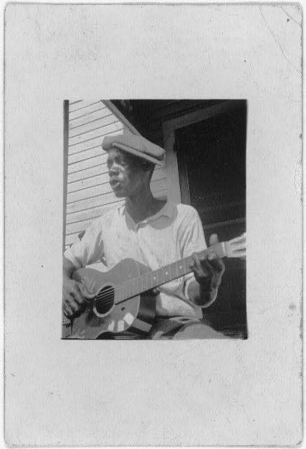 [Bill Tatnall, half-length portrait, seated, facing left, playing guitar, Frederica, Georgia]