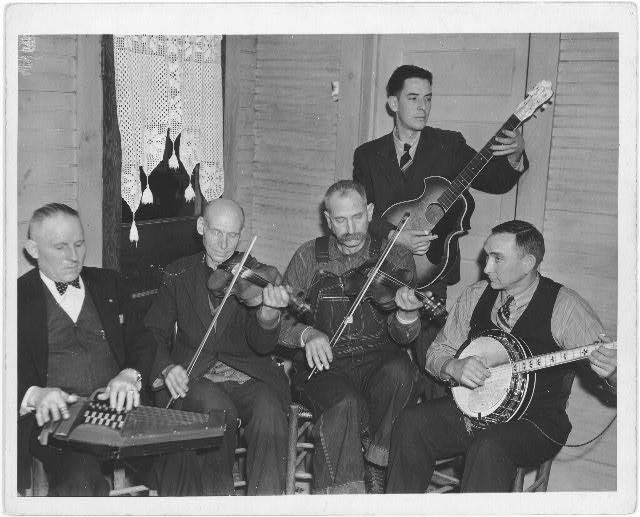 [Members of the Bog Trotters Band seated playing or holding instruments, Galax, Va. Includes band leader, Doc Davis, with autoharp; Uncle Alex Dunford with fiddle; Crockett Ward with fiddle; Wade Ward with banjo; Fields Ward with guitar]