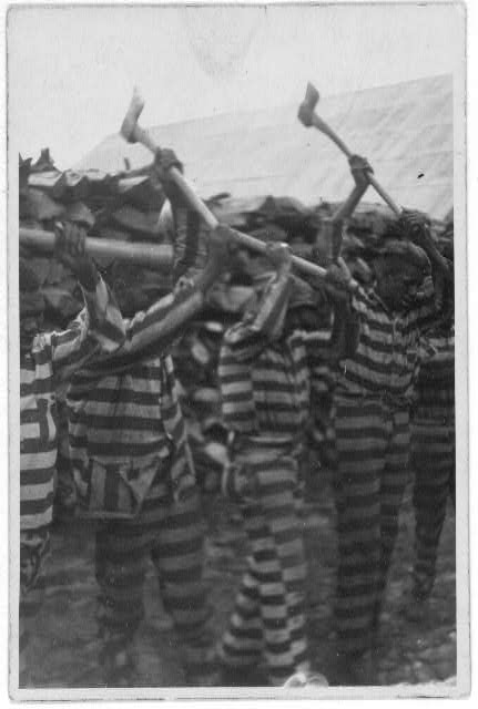 [African American convicts working with axes and singing in woodyard, Reed Camp, South Carolina]