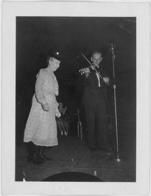 [Fiddling Bill Hensley, playing fiddle, and unidentified woman at the Mountain Music Festival, Asheville, North Carolina]