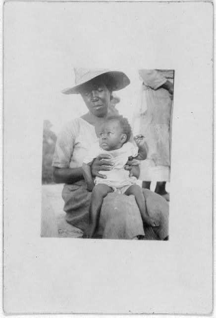 [Woman holding child on her lap, Old Bight, Cat Island, Bahamas]