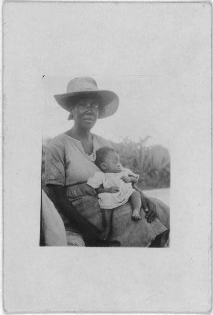 [Woman sitting and holding infant, Cat Island, Bahamas, July 1935]