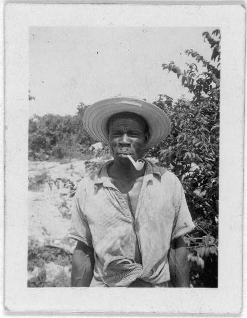 [Man standing, half-length, with pipe, possibly from the visit by Alan Lomax and Mary Elizabeth Barnicle to Andros Island in the Bahamas]
