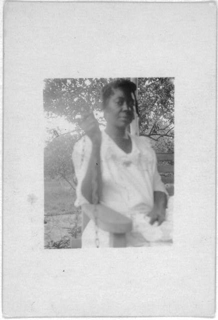 [Woman seated in porch swing, Eatonville, Fla., taken during the Lomax, Hurston, Barnicle 1935 expedition to Georgia, Florida and the Bahamas]