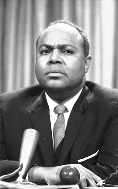 [James Farmer at a meeting of American Society of Newspaper Editors, bust portrait, seated at a table before a microphone]