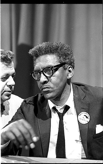 [Bayard Rustin at news briefing on the Civil Rights March on Washington in the Statler Hotel, half-length portrait, seated at table]
