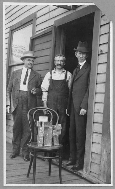 Delegate Wickersham, the assayer and Frank G. Carpenter in front of Assayer's Office