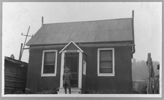 [Uniformed man in front of house, Yukon River area]