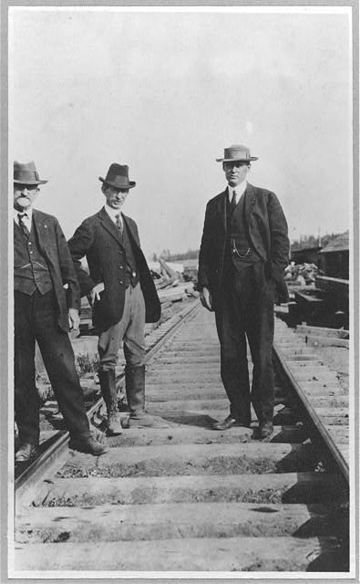 At the new railroad left to right are: Mr. Edes, Frank G. Carpenter, Lieut. Mears