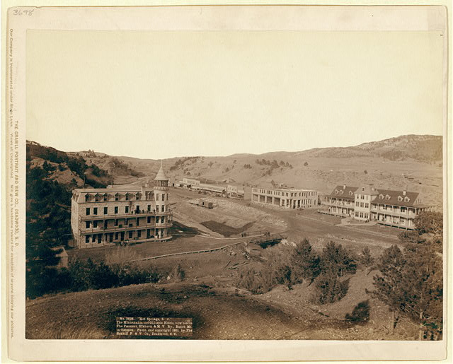 """Hot Springs, S.D."" The Minnekahta and Gillispie Hotels, new blocks.  The Fremont, Elkhorn & M.V. Ry., Battle Mt. in distance"