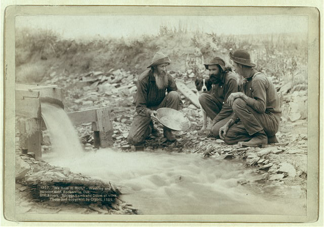 """We have it rich."" Washing and panning gold, Rockerville, Dak. Old timers, Spriggs, Lamb and Dillon at work"