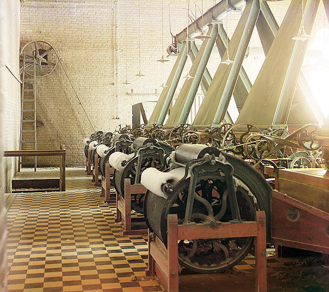 [Cotton textile mill interior with machines producing cotton thread, probably in Tashkent]