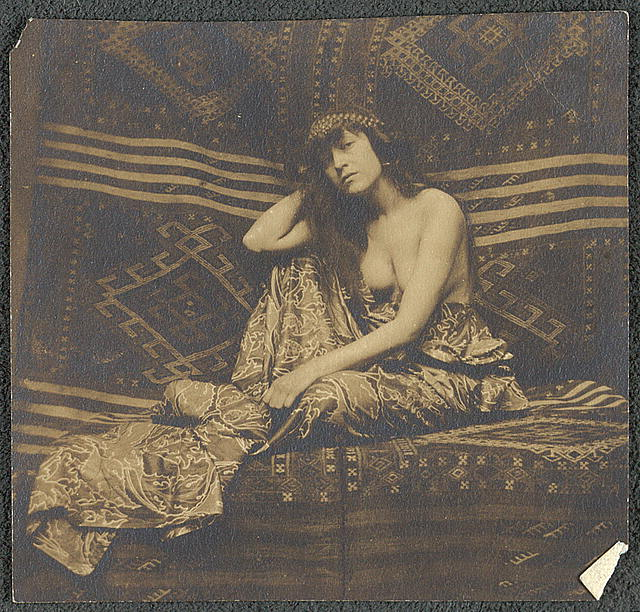 [Portrait of a woman, partially draped, seated on a sofa]