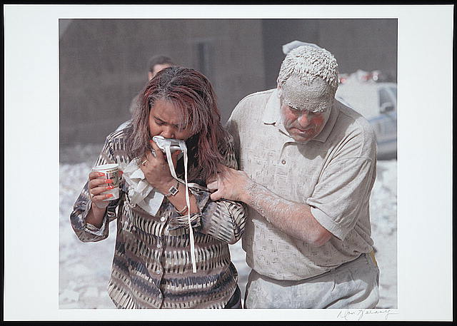 [Man covered with ashes assisting a woman walking and holding a particle mask to her face, following the September 11th terrorist attack on the World Trade Center, New York City]