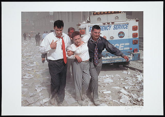 [Two men assisting and walking with an injured woman down a street littered with paper and ashes, following the September 11th terrorist attack on the World Trade Center, New York City]