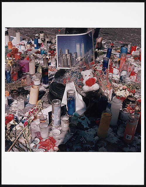 [Memorial for the victims of the September 11th terrorist attack on the World Trade Center, New York City; with candles, flowers, mementos, and photo of the twin towers]