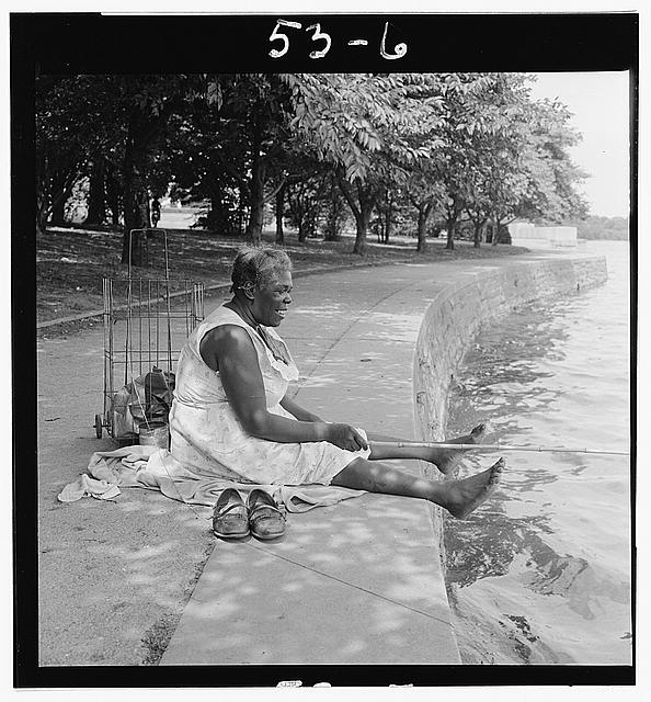 [African American woman, seated on ground, fishing, at the Tidal Basin, Washington, D.C.]