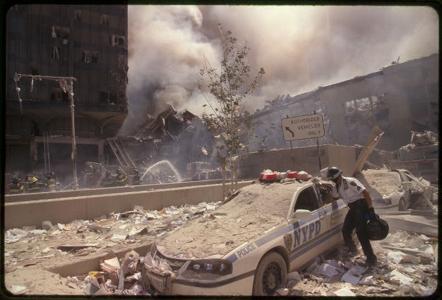 [Rescue worker reaching into a New York Police car covered with debris while New York City fire fighters spray water on smoldering ruins in background, following September 11th terrorist attack on World Trade Center, New York City]