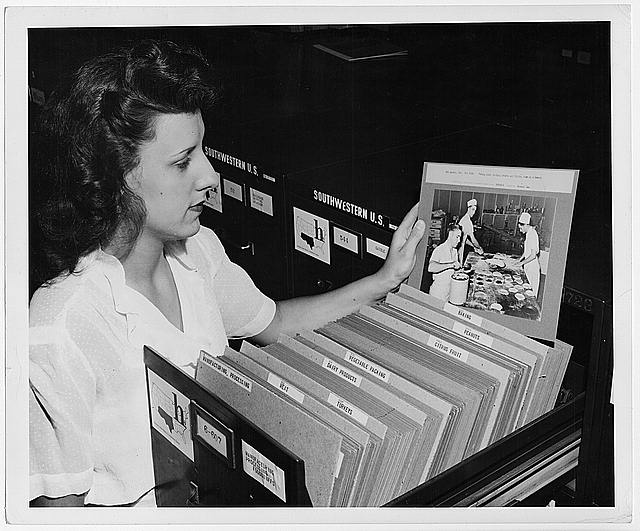 Jeannette Poirier looking at photograph of baking in file cabinet drawer at the Washington office of the Overseas Branch of the U.S. Office of War information