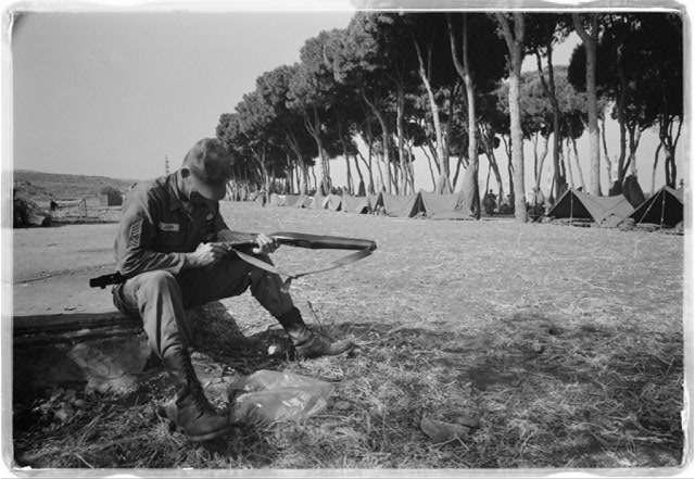 [American paratrooper cleans his gun at Army base camp in Beirut, Lebanon]