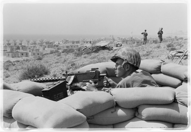 [U.S. Marine sits in a foxhole and points a machine gun towards Beirut, Lebanon, in the distance]