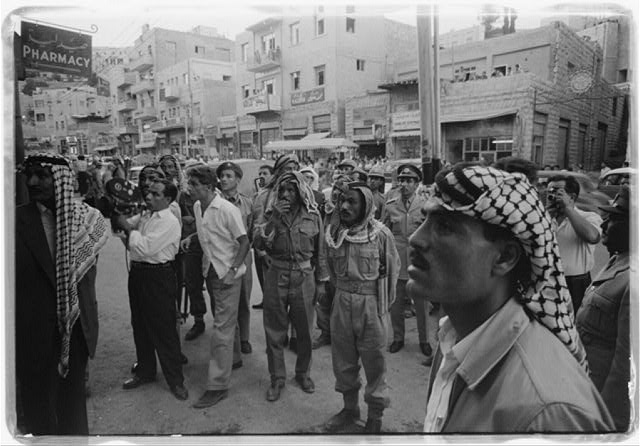 [Men gathered on a street in Amman, Jordan]