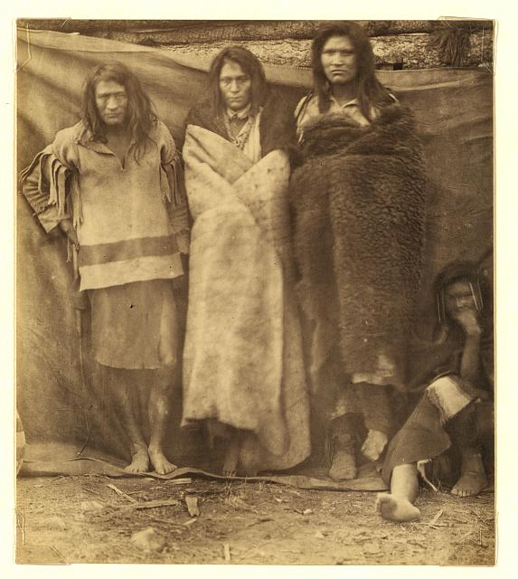 [Group of Native Americans, three standing, one seated on the ground, possibly Colville or Kutenai, at the winter quarters of the British Northwest Boundary Commission Survey in Colville, Washington]