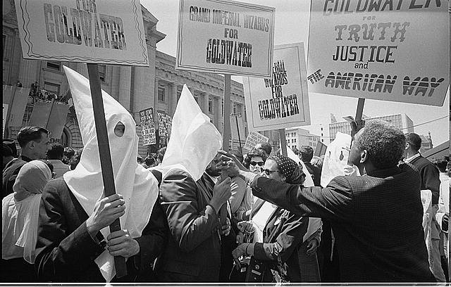 [Ku Klux Klan members supporting Barry Goldwater's campaign for the presidential nomination at the Republican National Convention, San Francisco, California, as an African American man pushes signs back]