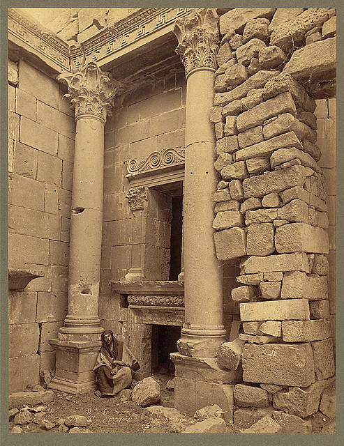 [Man seated at base of column outside entrance to building, al Bara]
