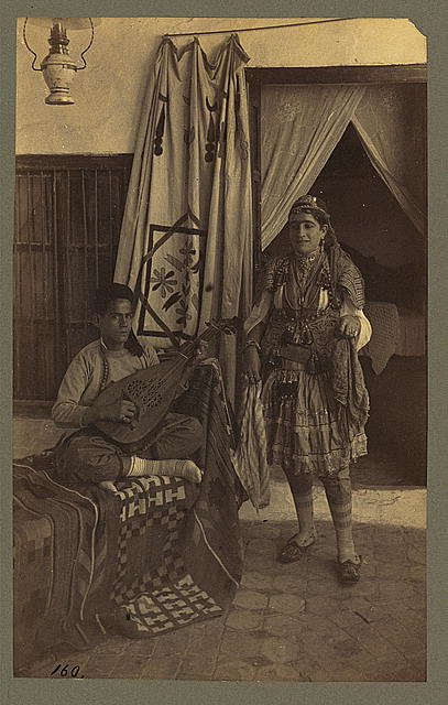 [Young man seated, playing an oud, while a young woman stands nearby]
