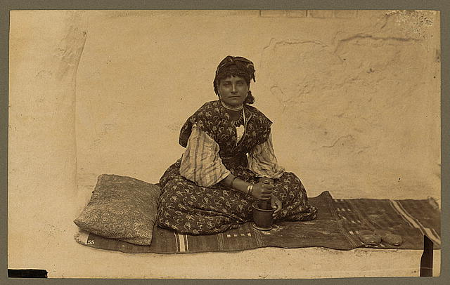 [Woman, full-length portrait, seated on rug on ground, facing front, using mortar and pestle, Constantine, Algeria]