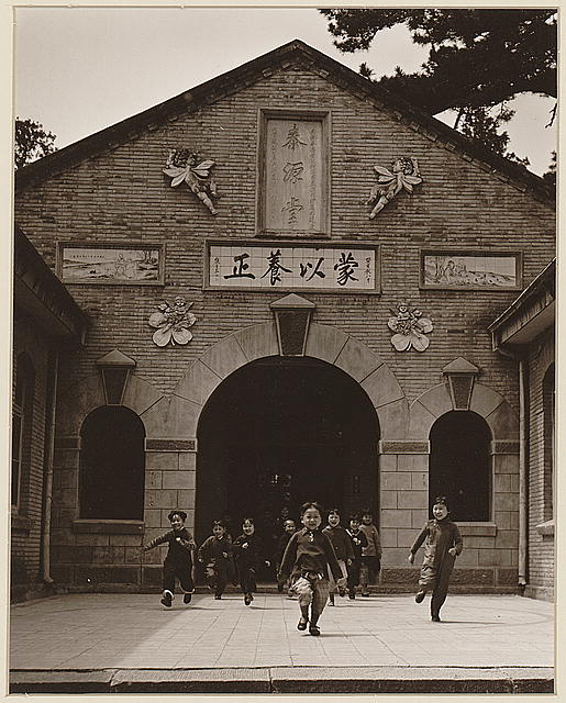 [Smiling young school children running out the entrance of a school building in the Kiangsu Province or Yunnan Province in China]
