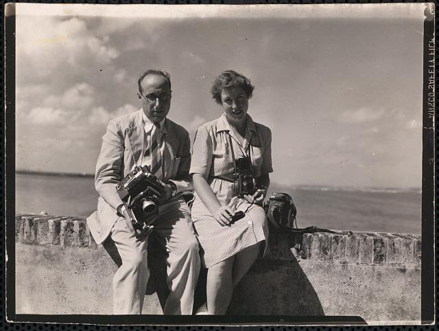 [Portrait of Edwin and Louise Rosskam, full-length, posed with cameras, sitting on a wall by the sea, Puerto Rico]