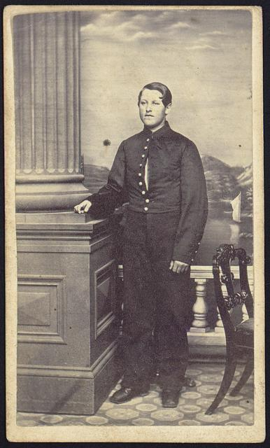 [Unidentified young man, full-length studio portrait, standing in front of painted backdrop, facing front, wearing military uniform]