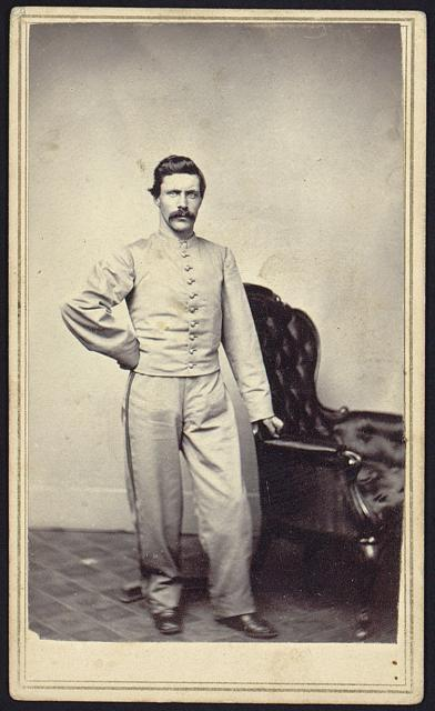[Portrait of Jesse F. Stimpson, a bugler, full-length studio portrait, standing next to chair, facing front, wearing band(?) uniform]