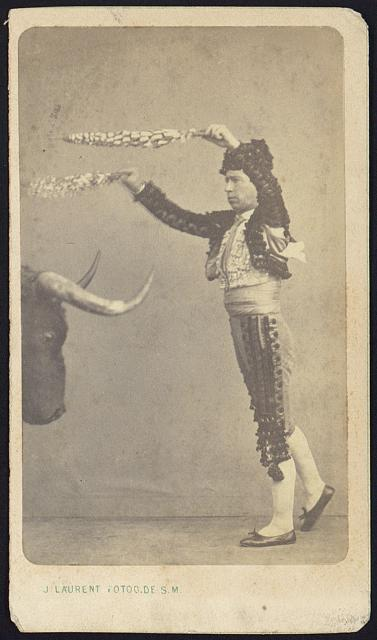 [Unidentified matador, full-length portrait, facing left, standing in front of the head of a bull]