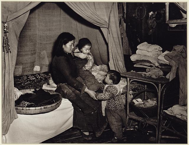 [Mother with two young children in sleeping area of dwelling in the Kiangsu Province or Yunnan Province in China]
