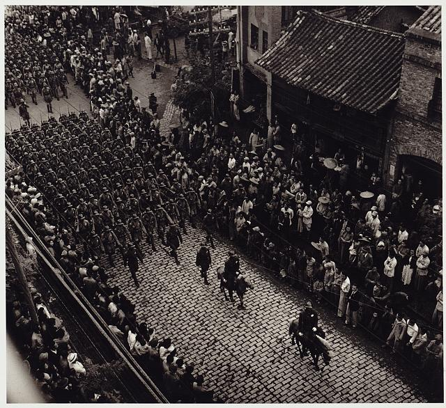 [View from above of provincial troops marching along city street in the Kiangsu Province or Yunnan Province in China]
